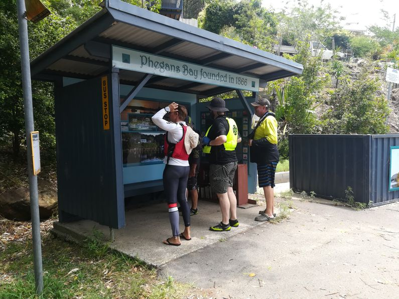 Paddlers looking at bus stop at Phegans Bay