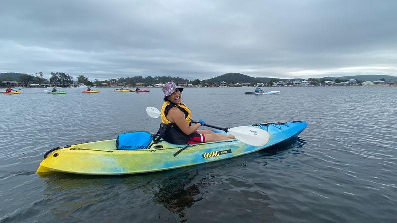 Chloe paddling in a kayak past Davistown