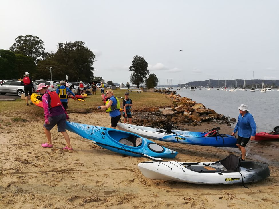 Kayaks line up on beach after paddling
