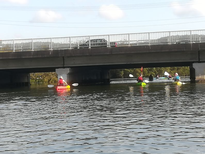Paddlers moving under the bridge over the Central Coast Highway